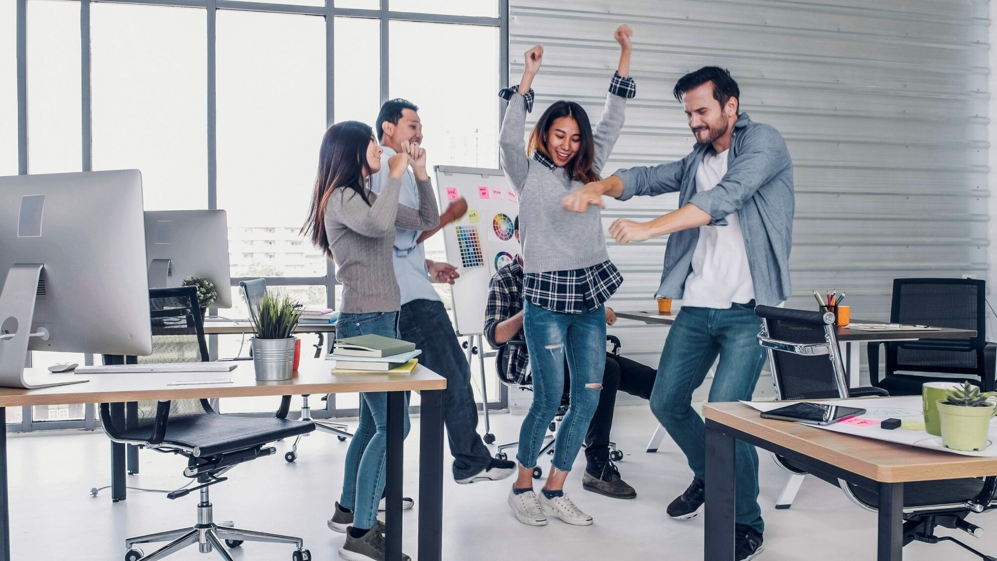 Digitalbyrå i Stockholm - group of creative designer dancing in office with relax feeling and glad about good success news of project at modern office.business day work lifestyle.